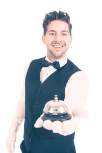 Portrait of smiling young waitperson holding service bell over white background